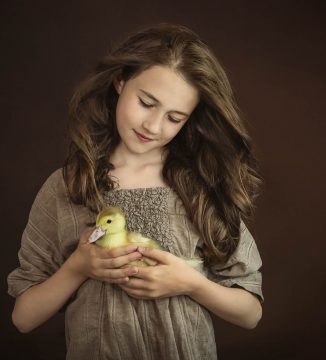 portrait of girl holding a pet duckling