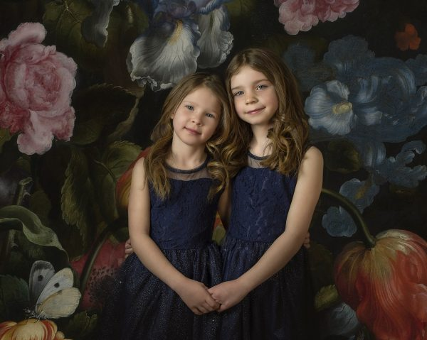 Portrait of two sisters in blue dresses with vintage floral digital background