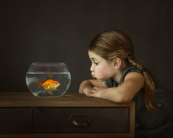 portrait of girl with braids in hair making fish lip face at pet goldfish