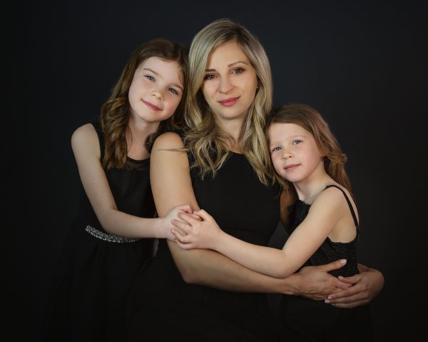 A traditional studio family portrait of a mother and two daughters